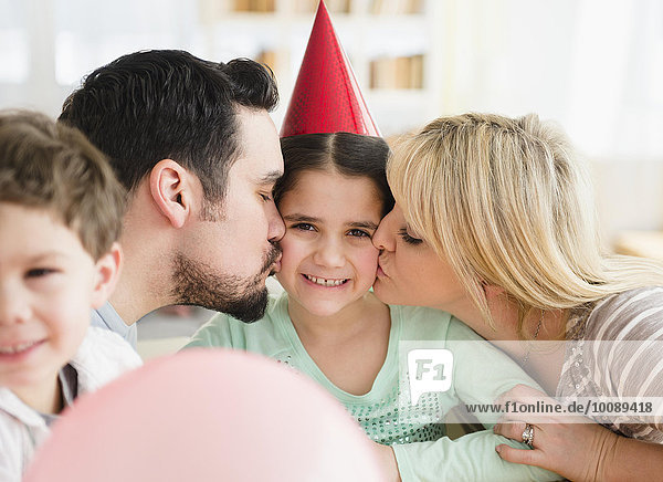 Caucasian parents kissing daughter at birthday party