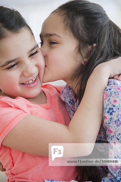 Close up of Caucasian sisters kissing