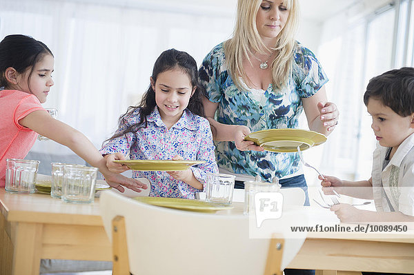 Caucasian mother and children setting table