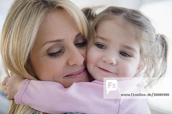 Close up of Caucasian mother hugging daughter