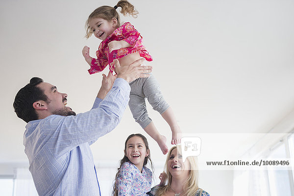 Caucasian father tossing daughter in air