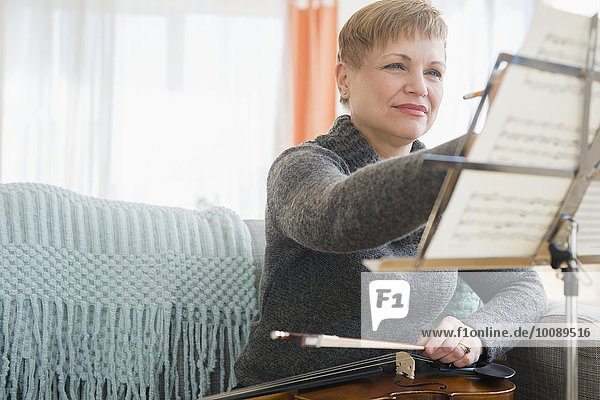 Caucasian violinist writing on sheet music