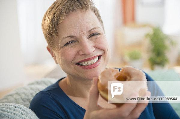 Smiling Caucasian woman eating donut