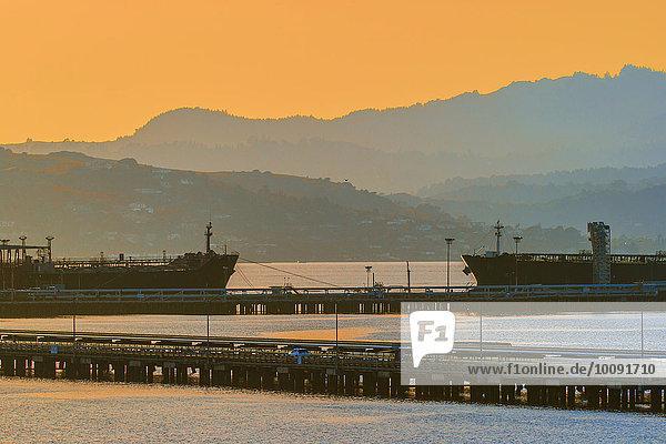 Silhouette der Hügel über Industriehafen