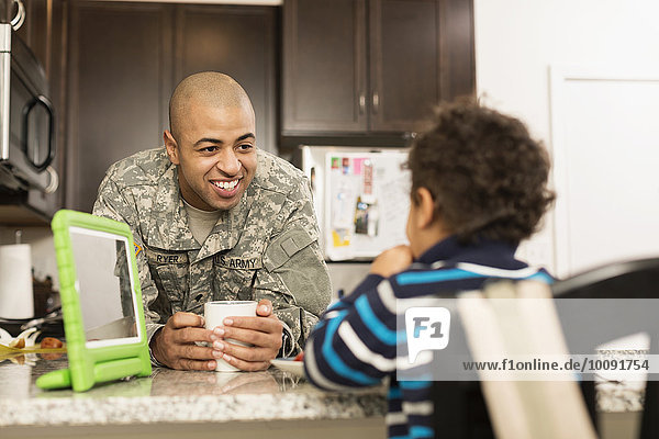 Mixed race soldier father and son eating in kitchen