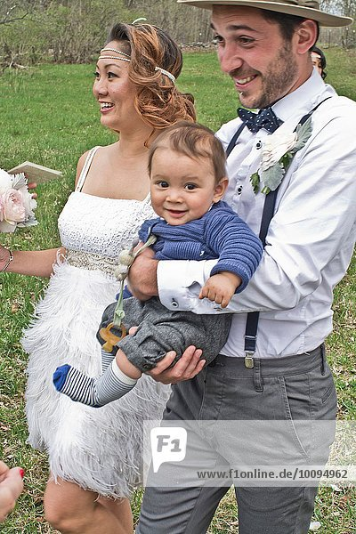 Bride and groom walking across field with baby boy