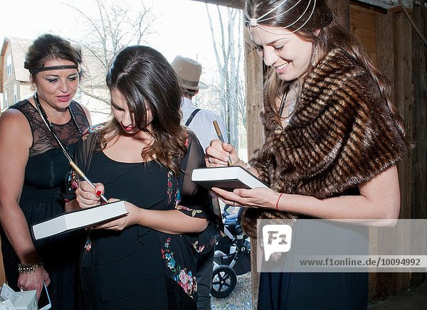 Female wedding guests writing messages on books