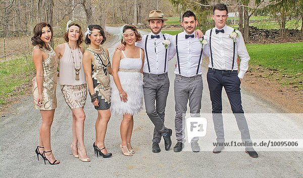 Portrait of bride and groom standing with friends