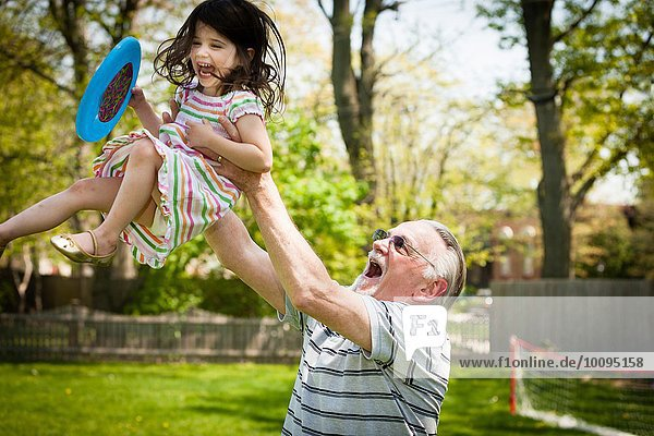 Grandfather and granddaughter playing in garden