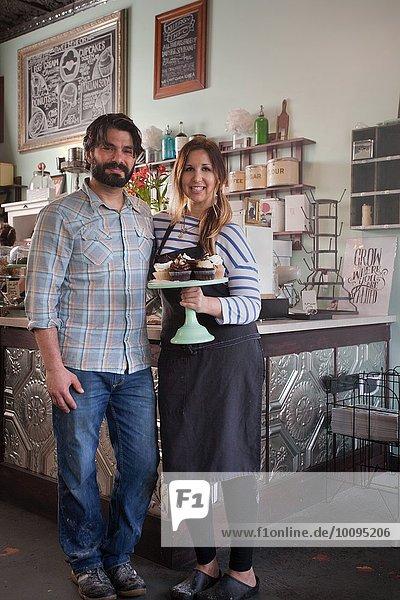 Bäckereibesitzer tragen Tablett mit allergikerfreundlichen Cupcakes