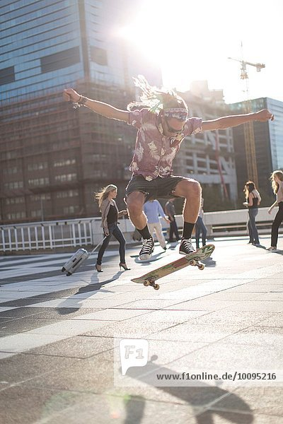 Skateboarder performing trick in urban area