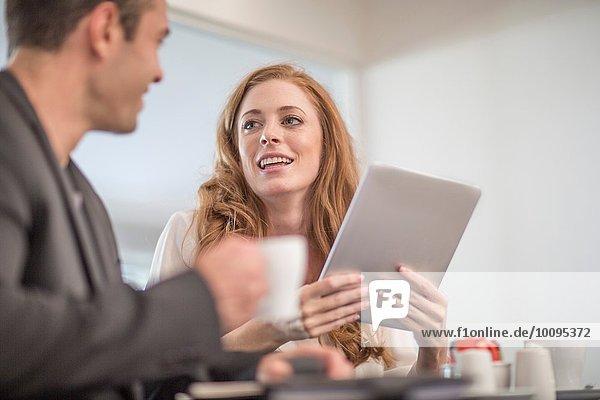 Geschäftsleute mit digitalem Tablett beim Geschäftsessen