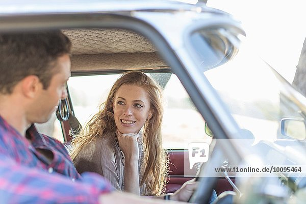Heterosexuelles Paar im Auto zusammen  lächelnd