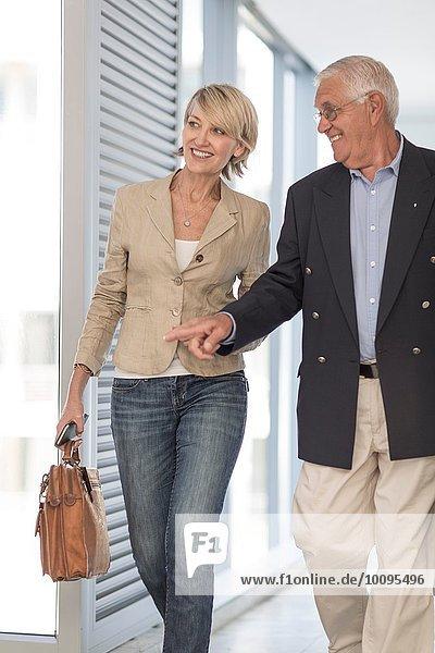 Reife Geschäftsfrau und Mann auf dem Hotelgang