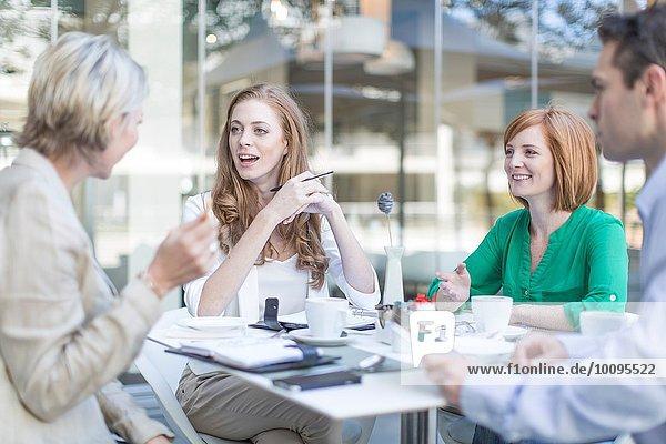 Treffen von Geschäftsfrauen und Männern bei einer Kaffeepause auf der Hotelterrasse