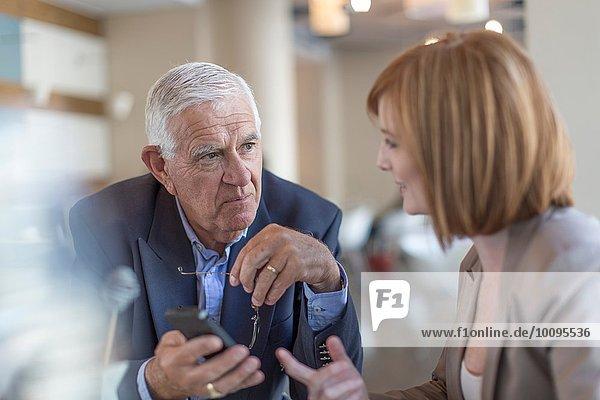 Senior Geschäftsmann Smartphone Text an Kollegen am Frühstückstisch im Hotelrestaurant