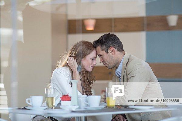 Romantisches Geschäftspaar Kopf an Kopf am Hotelfrühstückstisch