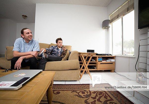 Zwei junge Männer sitzen auf dem Sofa und schauen fern.