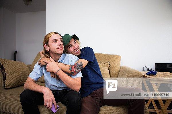 Zwei junge Männer sitzen auf dem Sofa und umarmen sich.