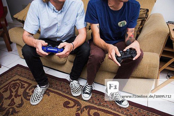 Zwei junge Männer sitzen auf dem Sofa  spielen Videospiel  niedriger Abschnitt