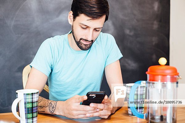 Junger Mann am Tisch sitzend  Kaffee trinkend  Smartphone anschauend