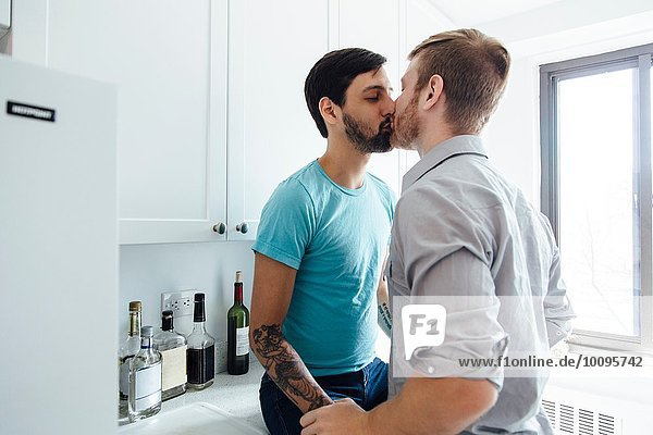 Male couple kissing in kitchen