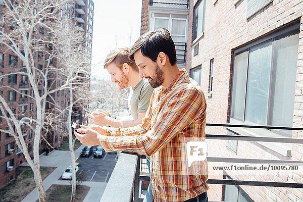 Männliches Paar auf dem Balkon stehend  mit Blick auf Smartphones