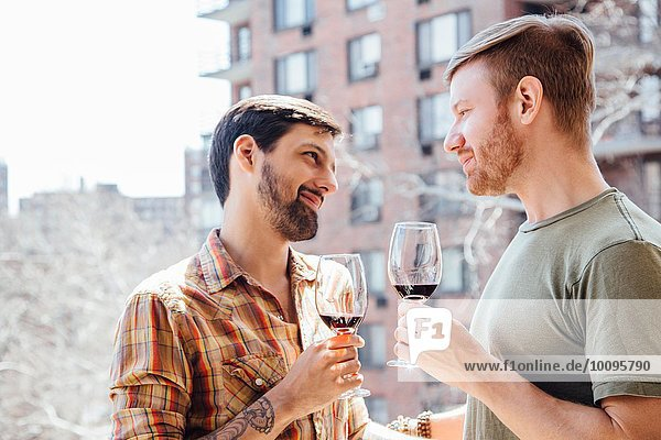Male couple standing on balcony  holding wine glasses  face to face