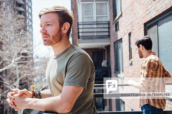 Männliches Paar auf dem Balkon stehend  voneinander entfernt  mit traurigem Ausdruck