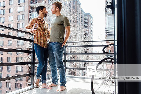 Male couple standing on balcony  face to face