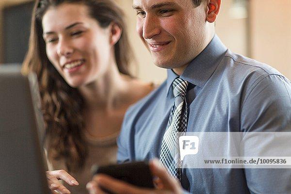 Junges Paar beim Durchstöbern von Laptop und Smartphone zu Hause