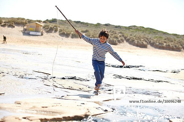 Young boy running along sand with stick