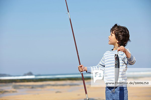 Young boy holding up fishing rod and fish