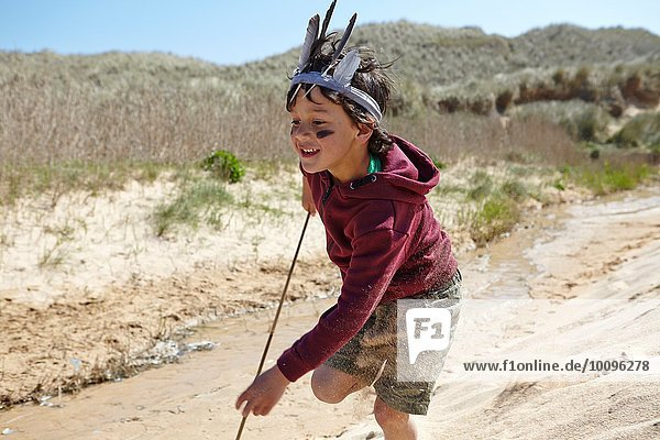 Young boy  wearing fancy dress  running on sand