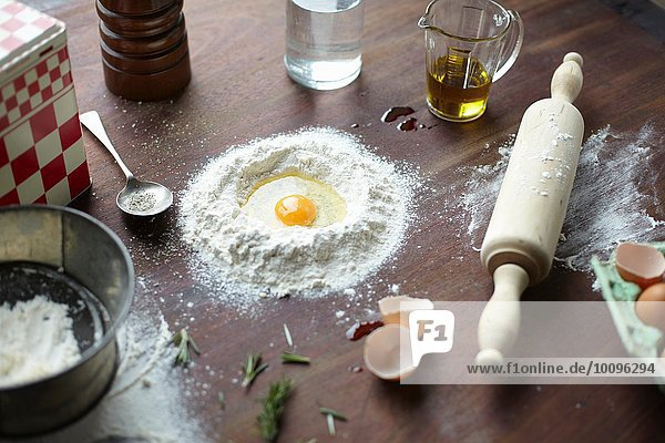 Table with raw egg in center of flour stack and kitchen utensils