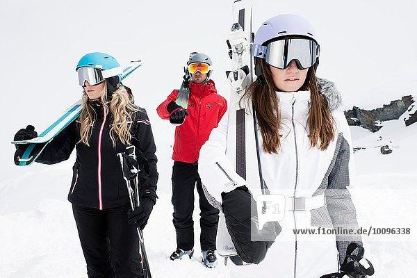 Freunde mit Helm und Skibrille mit Skiern  Portrait