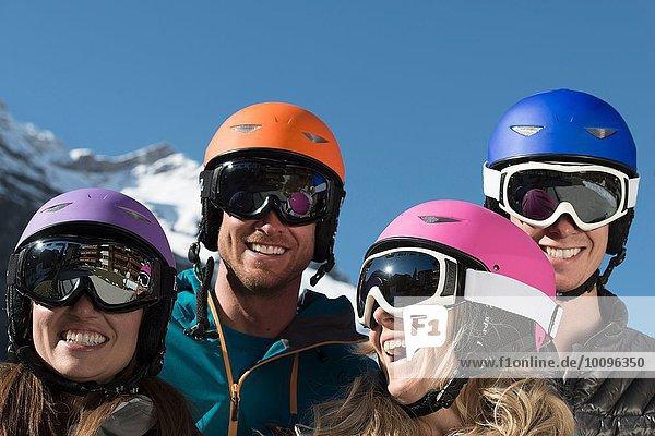 Vier Freunde mit Skihelmen und Schutzbrille  lachend