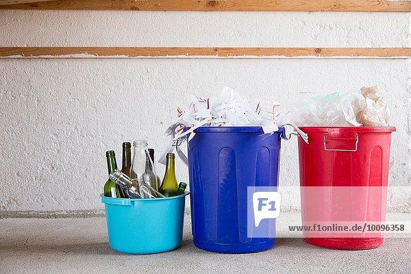 Drei Recycling-Eimer in der Garage mit Flaschen  Papier und Plastik