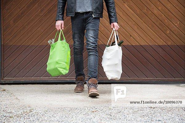 Teenager-Junge mit wiederverwendbaren Einkaufstaschen voller leerer Flaschen für das Recycling