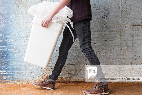 Teenager-Junge trägt Mülltonne mit recycelbarem Papierabfall