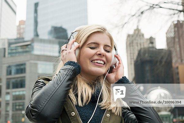 Portrait einer jungen Frau auf der Straße  die Kopfhörer mit geschlossenen Augen hört  New York  USA