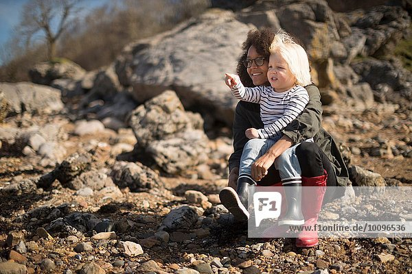 Mother and son crouching on rocks