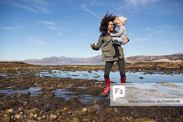 Mutter mit Sohn beim Springen in Loch Eishort  Isle of Skye  Hebrides  Schottland