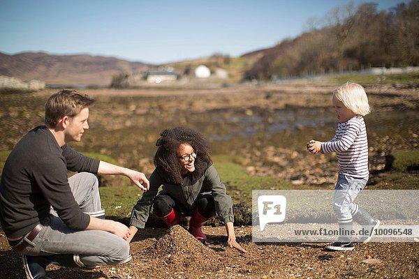 Mutter und Vater spielen mit dem Sohn und bilden einen Haufen Erde.