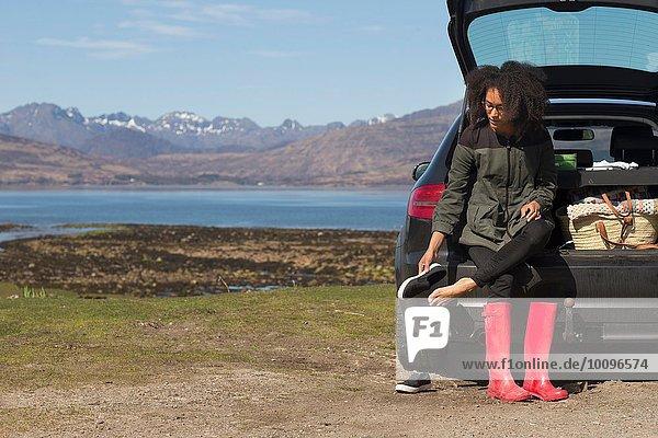 Mittlere erwachsene Frau  die auf dem Kofferraum sitzt und Schuhe anzieht  Loch Eishort  Isle of Skye  Hebrides  Schottland