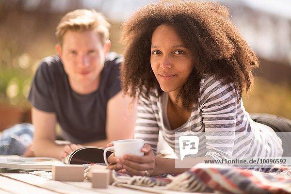 Mittleres erwachsenes Paar entspannt sich im Freien  Frau schaut auf die Kamera
