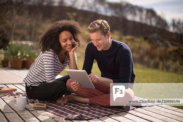 Mittleres erwachsenes Paar auf der Decke sitzend mit Tablette