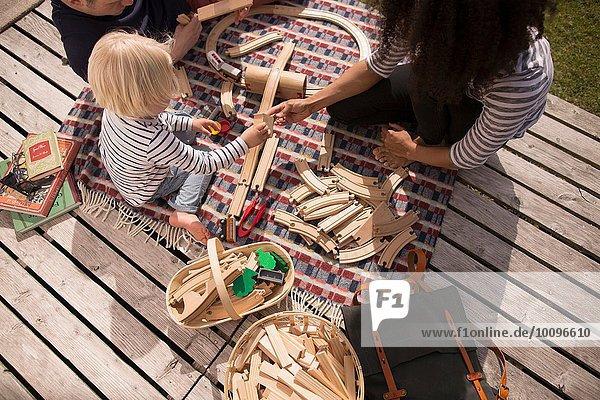 Mutter und Sohn spielen mit Holzspielzeugeisenbahn  hoher Winkel