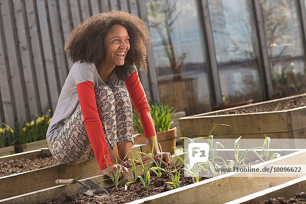 Mittlere erwachsene Frau auf einem erhöhten Pflanzenbeet sitzend  lächelnd