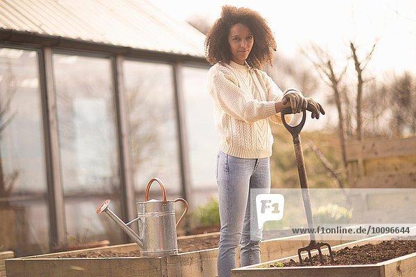 Mittlere erwachsene Frau bei Hochbett mit Gartengabel  Portrait